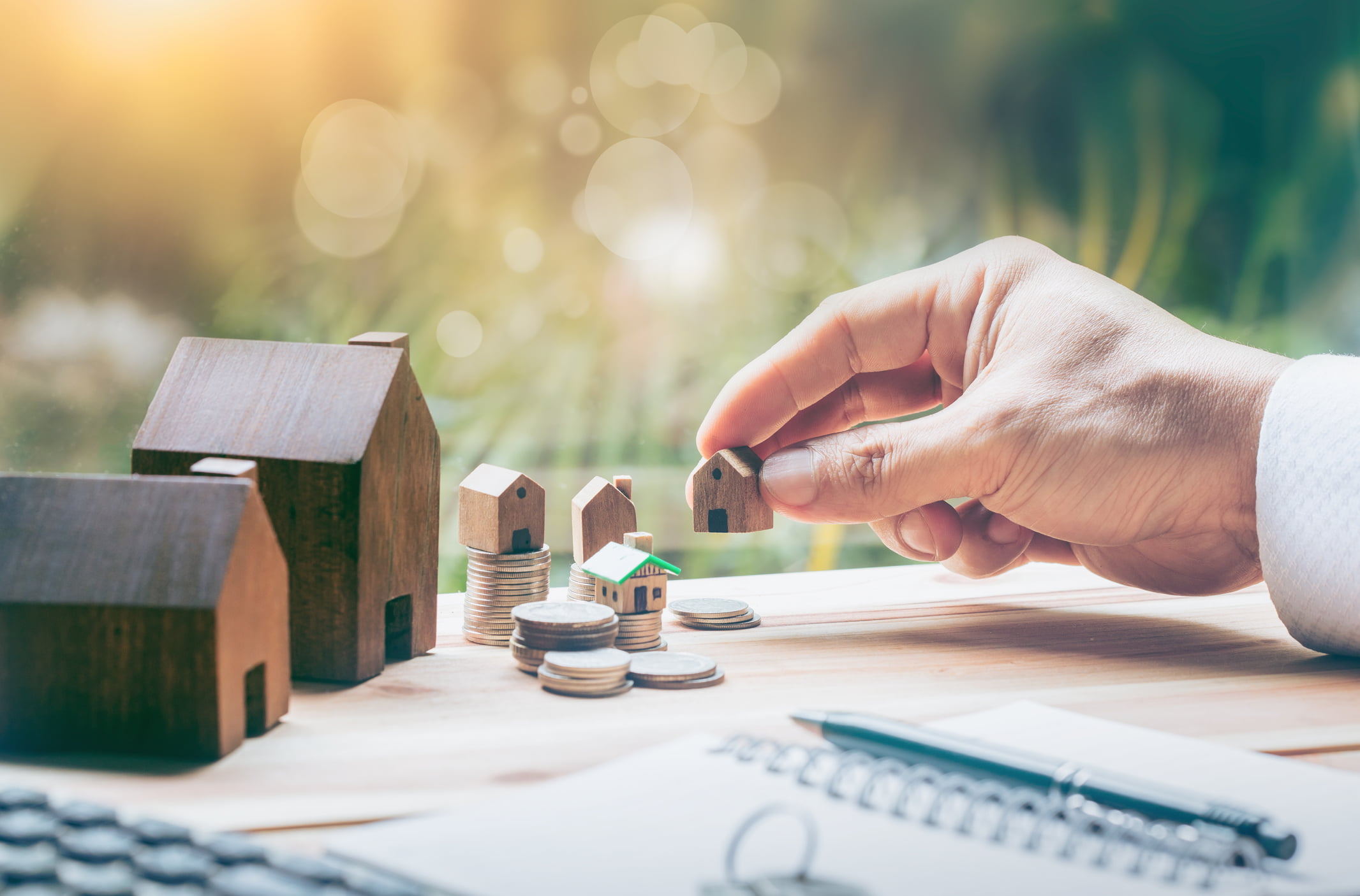 Calvert Home Mortgage | House placed on coins Men's hand is planning savings money of coins to buy a home concept concept for property ladder, mortgage and real estate investment. for saving or investment for a house,